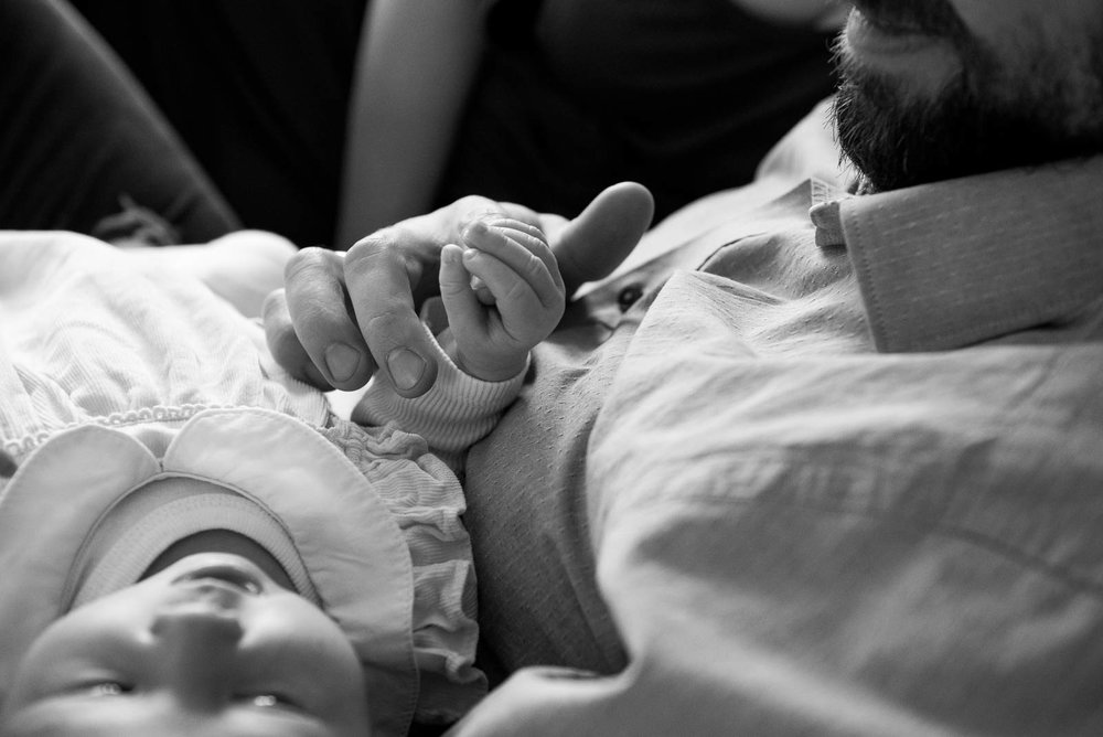 Father holding babies hand in family photography shoot