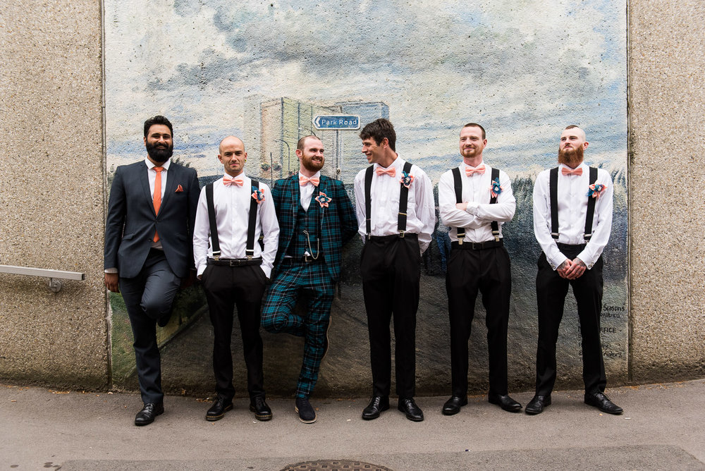 Alternative groom style with tartan suit and matching groomsmen braces and pink bow ties. © Jessica Grace Photography