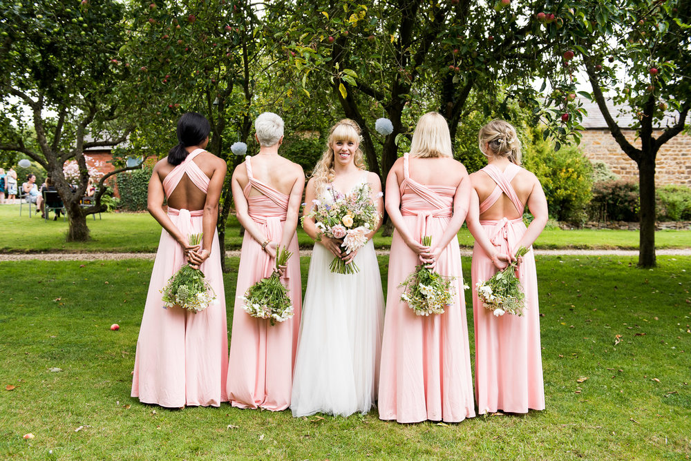 Styled group shot showcasing backs of the pretty bridesmaids dresses with wildflower bouquets by Bare Blooms © Jessica Grace Photography