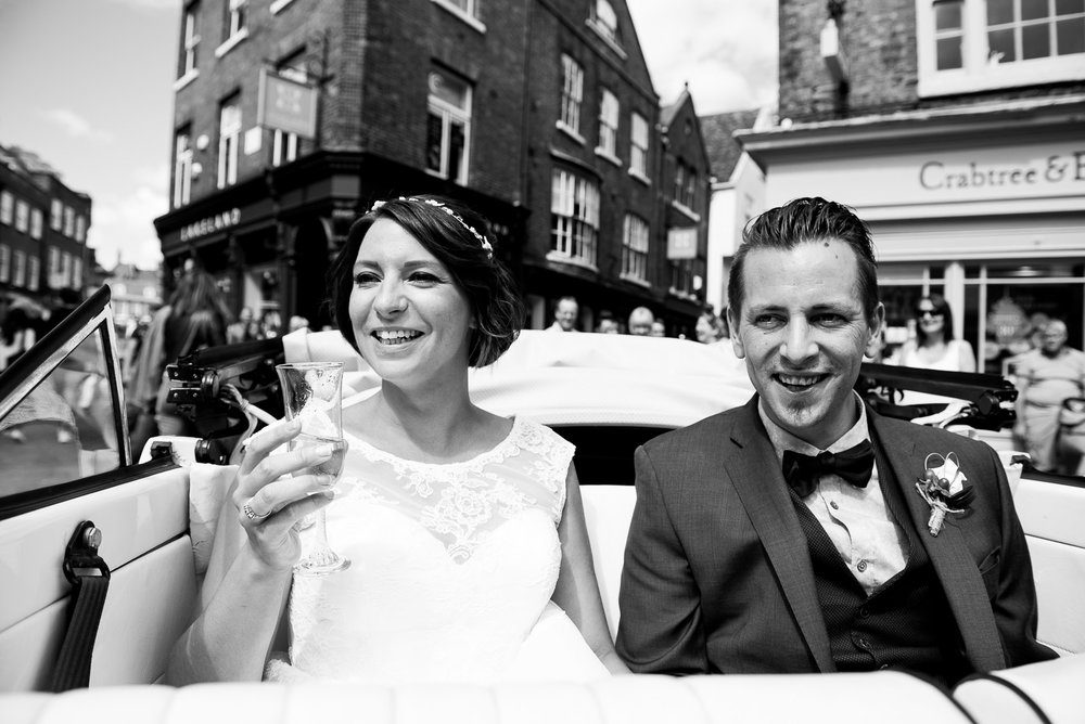 Gorgeous bride and groom enjoying open top car ride through York