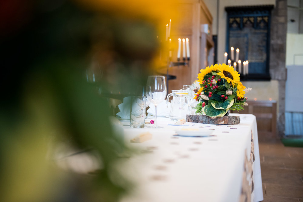 Pretty sunflower and red berry centre pieces to match bridal bouquets.