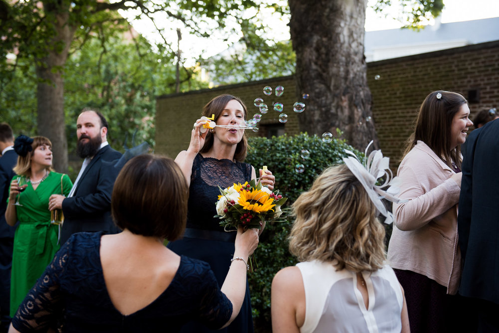 Fun, natural wedding moments. Playing with bubbles at the reception. © Jessica Grace Photography