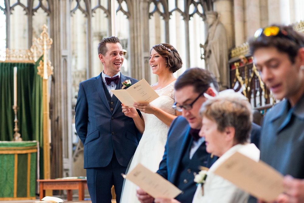 Natural wedding moment, bride and groom singing hymns in the York Minster. © Jessica Grace Photography