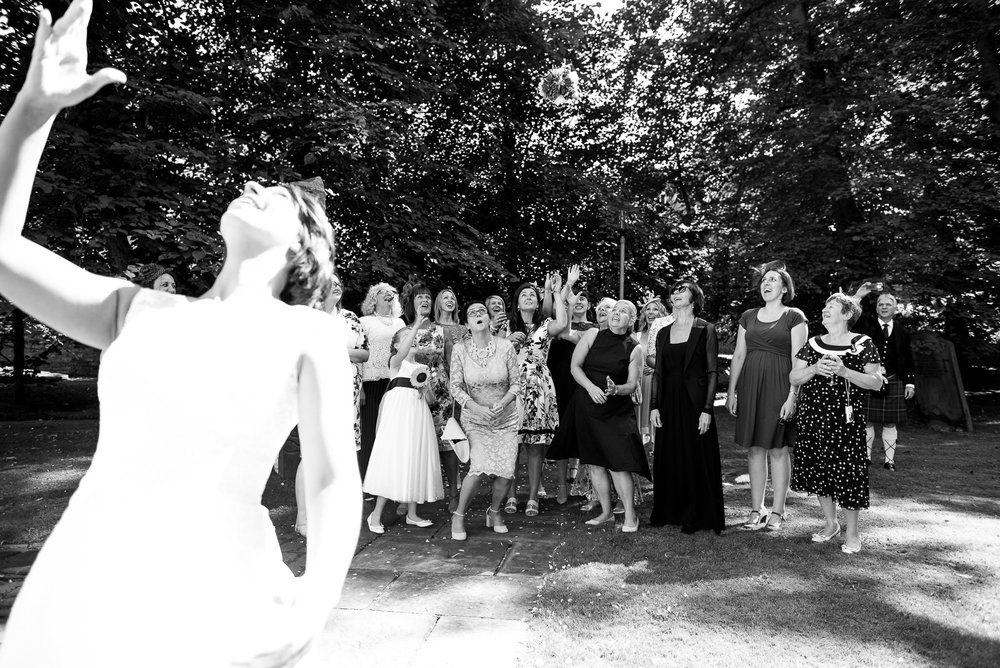 Bride throws the bouquet in the gardens of the National Centre for Early Music. York. © Jessica Grace Photography
