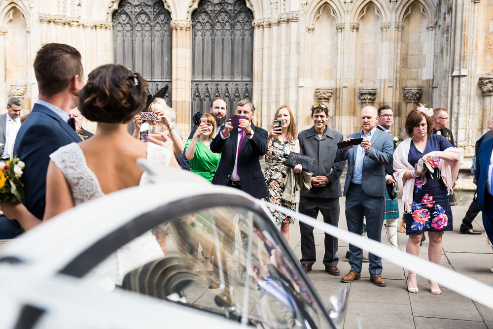 wedding guests taking photographs outside the minster.jpg