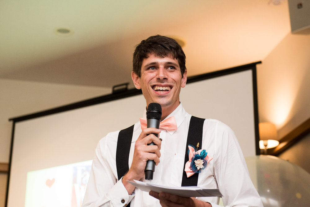 Handsom groomsmen giving a speech - with matching pink bowtie and handmade material button hole © Jessica Grace Photography