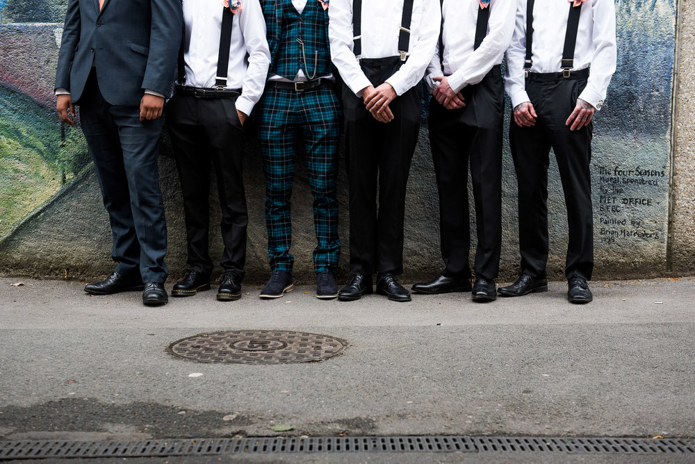 Groomsmen standing in a line with matching braces and a groom in a tartan ASOS suit © Jessica Grace Photography