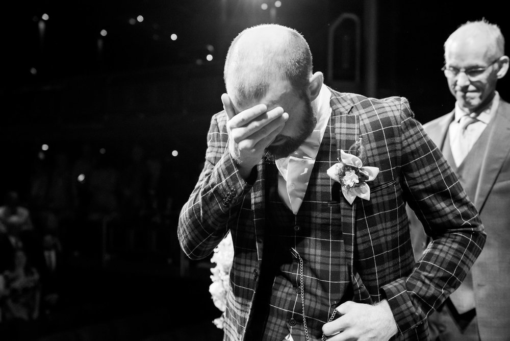 Emotional moment where the groom sees his bride for the first time - alternative wedding in a theatre, Surrey © Jessica Grace Photography