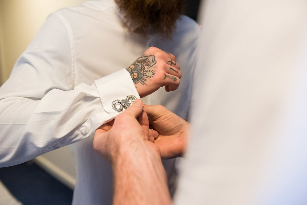 Tattooed groomsmen putting on vintage cufflinks Relaxed groom wearing an ASOS tartan suit for an Surrey wedding © Jessica Grace Photography