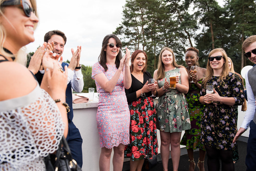 Guests reaction to a magic trick by wedding magician. Alternative outside wedding, Camberley Heath, Surrey © Jessica Grace Photography