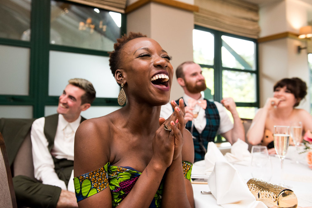 Gorgeous wedding guest laughing captivatingly at wedding speeches. Unobtrusive wedding photography, Surrey © Jessica Grace Photography