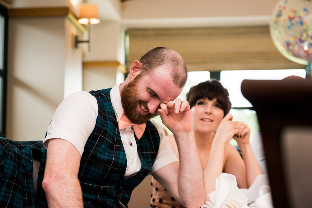 Captured moment - groom laughing at best man speech. Wearing ASOS tartan suit with matching pink bow tie © Jessica Grace Photography
