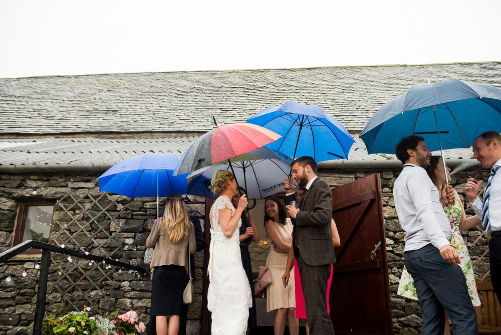Captured moment, creative wedding photography with umberellas to hide from the rain © Jessica Grace Photography