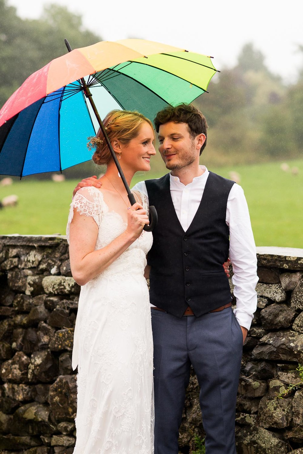 Couple embrace in the rain underneath a colourful rainbow umberella © Jessica Grace Photography