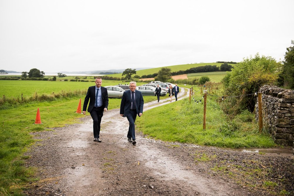 Guests arriving to the wedding ceremony on a wet Lake District day © Jessica Grace Photography
