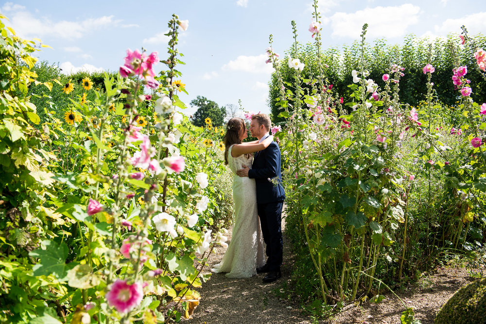 Bride and groom embrace in the beautiful gardens at Loseley Park, Surrey © Jessica Grace Photography