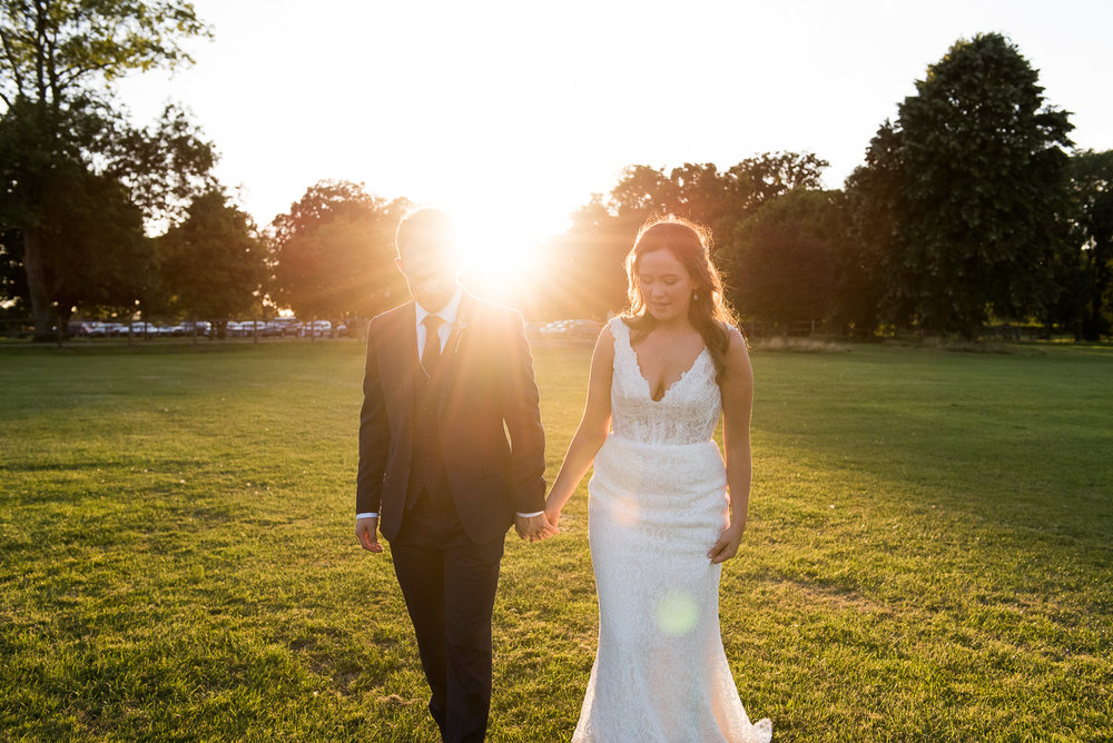 Bride and groom take a walk at sunset on the grounds of Loseley Park © Jessica Grace Photography