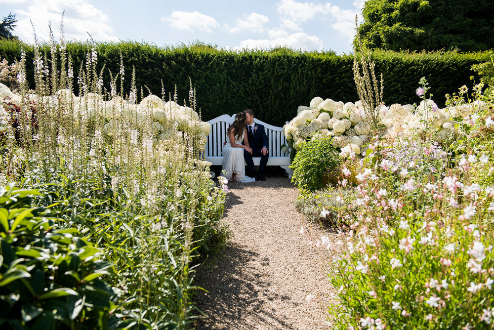Couple take a quiet moment in the white gardens at Loseley Park Bride and groom embrace in the beautiful grounds at Camberley Heath Golf Club, Surrey © Jessica Grace Photography