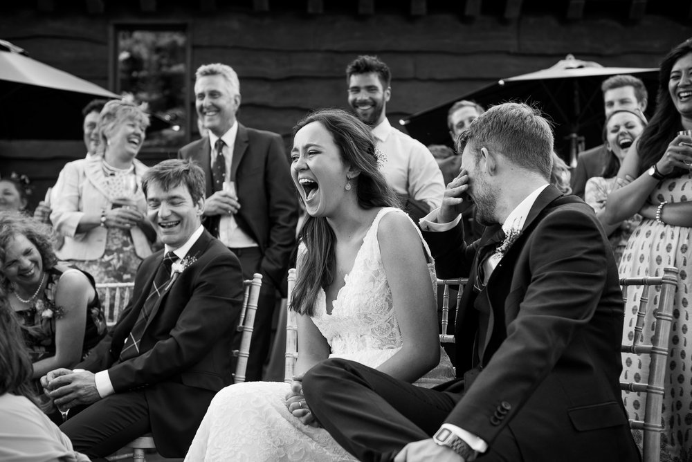 Gorgeous Maggie Sottero bride laughing with the groom during the best man speech © Jessica Grace Photography