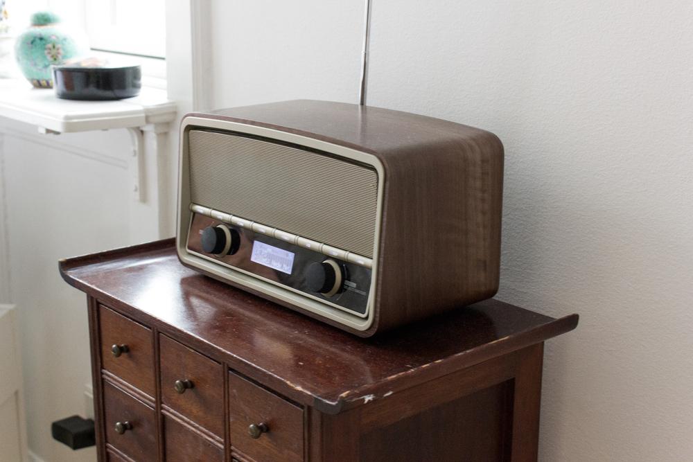 Fine detaljer i Nannas lejlighed. Radioen har et retro look, men er faktisk en nyere model. Til gengæld er den lille fine trækommode et fund, som Nannas forældre har gjort i et storskraldsrum.Wow, hvor heldig heldig har man lige lov at være?