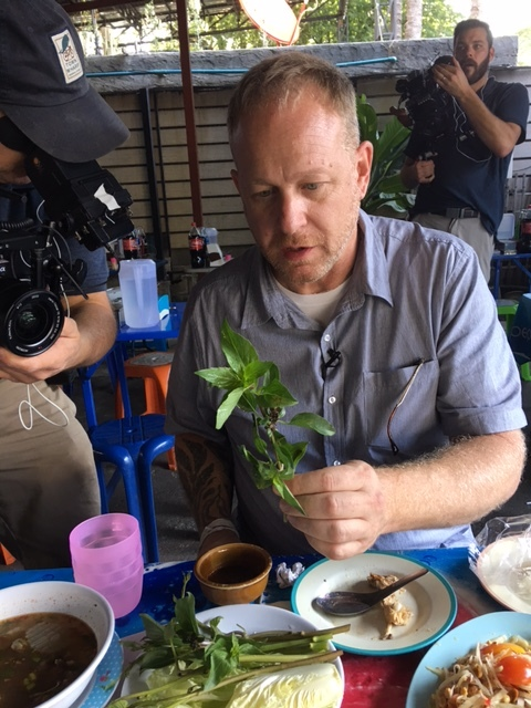 Andy shows Chris Thai basil at the grilled chicken restaurant. The restaurant also makes a terrific papaya salad using a wooden mortar and pestle to infuse the papaya with flavor.