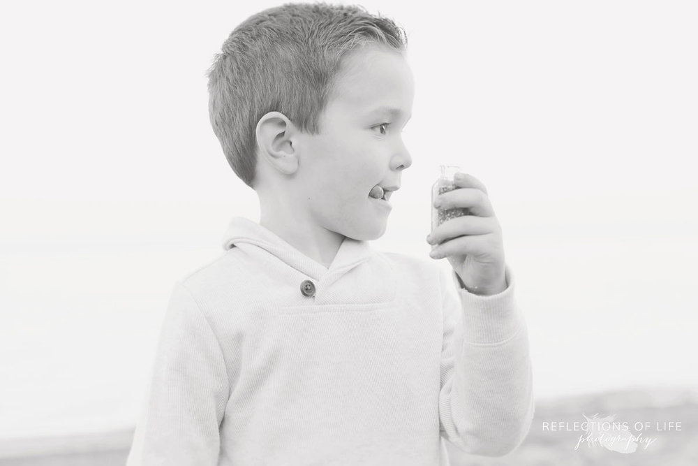 little boy playing with bubbles on the beach in niagara region of ontario canada