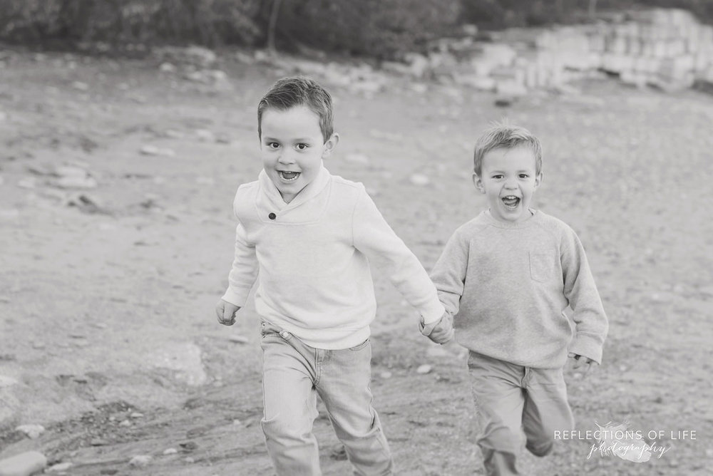 little boys running on the beach in niagara region of ontario canada