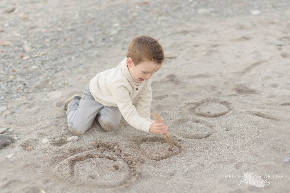 little boy playing on the sandy beach in southern ontario canada