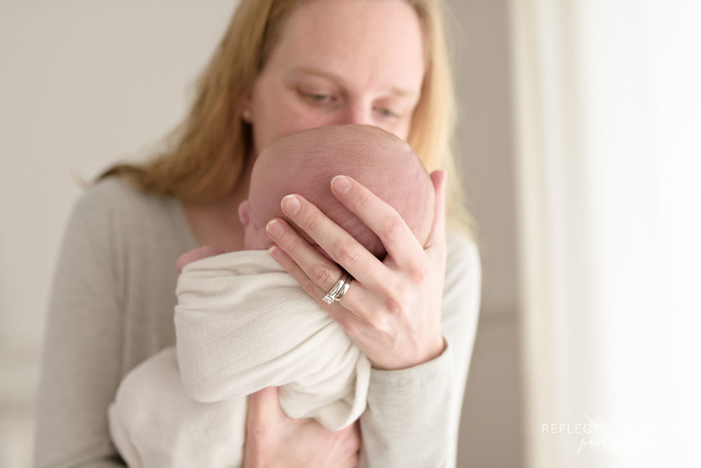 Mom leaning in and kissing her newborn baby in Niagara Newborn Photography studio