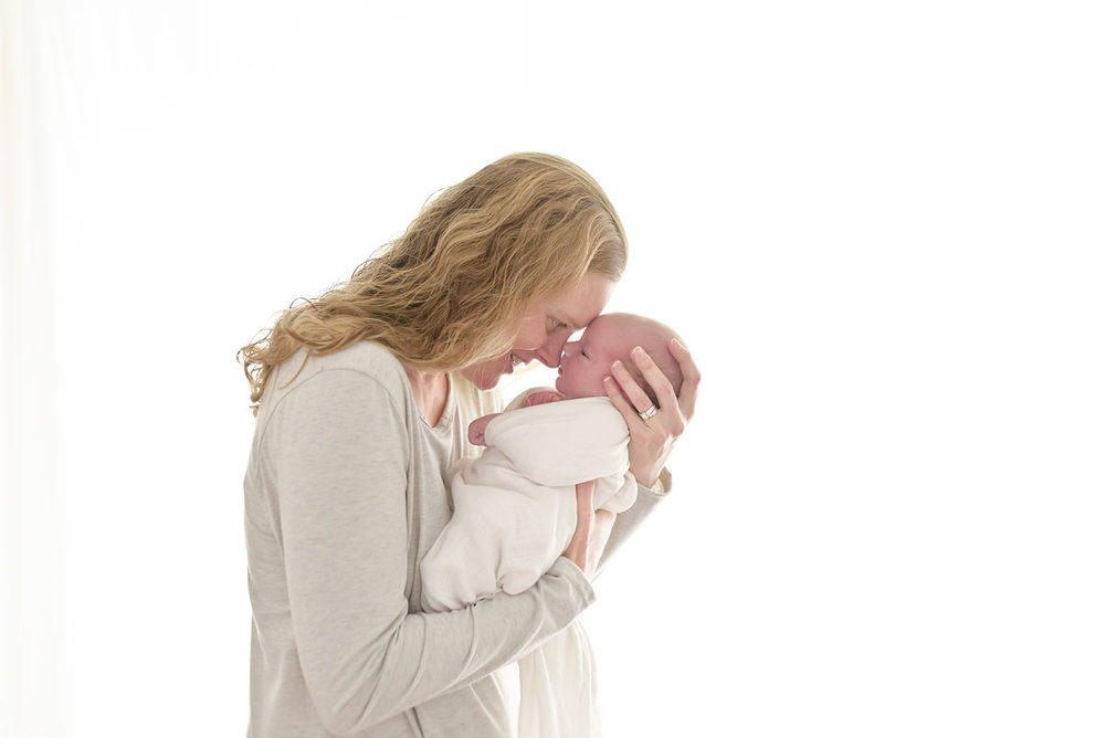 Mom totally in love with her newborn baby son in Niagara newborn photo studio