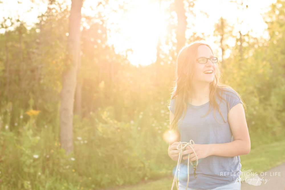 Candid image of girl walking down a path with sun shining though behind her