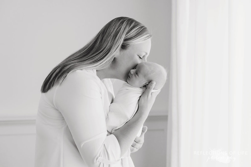 Mom whispering into ear of her newborn Niagara Newborn Photographer