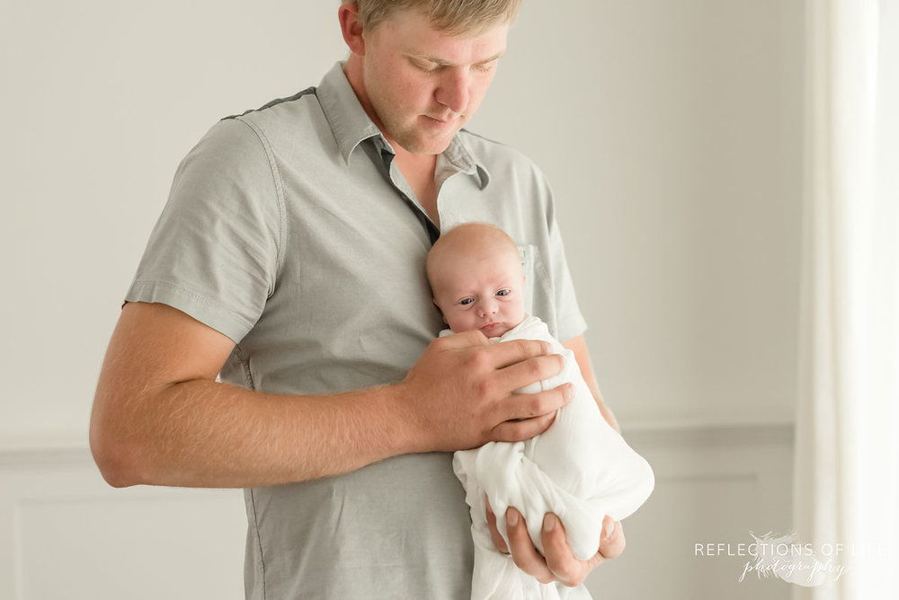 Portrait of dad holding baby boy by Toronto Baby Photographer