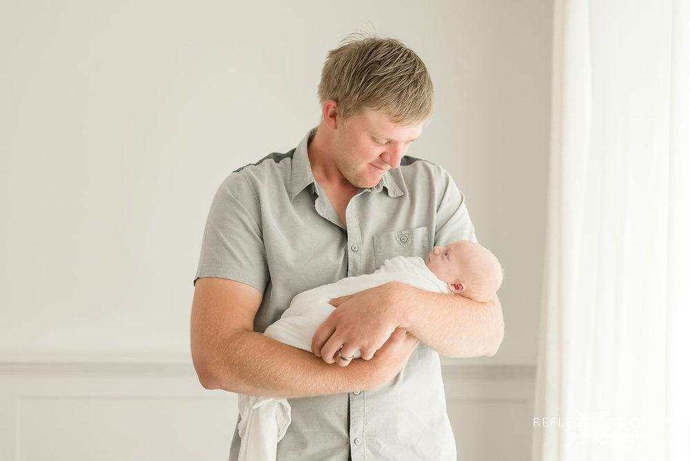 Dad looking down at newborn baby boy in Grimsby Ontario Photo Studio