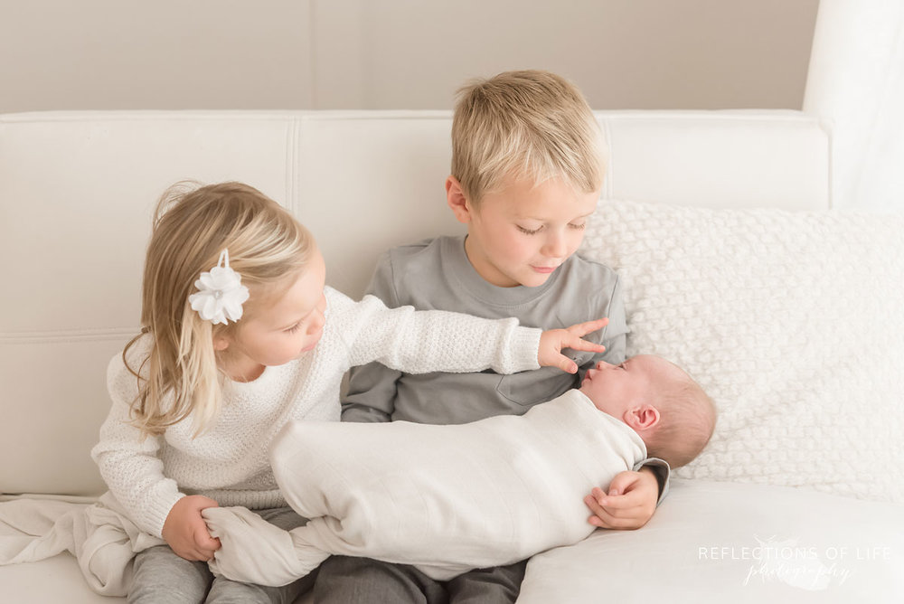 Family photo of siblings holding newborn baby sister