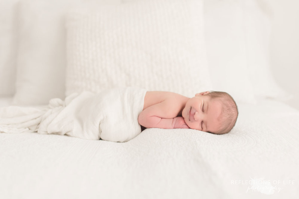 Colour photo of baby sleeping in white blanket