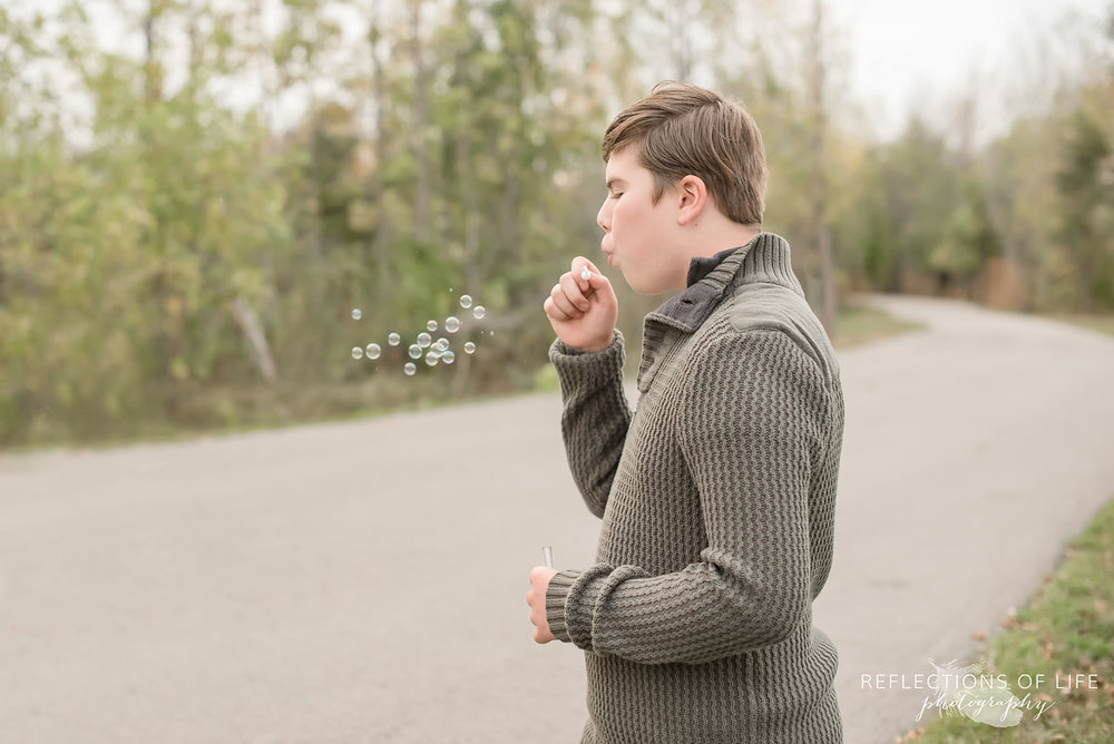 Teenage boy blowing bubbles on pathway in Grimsby Ontario.jpg