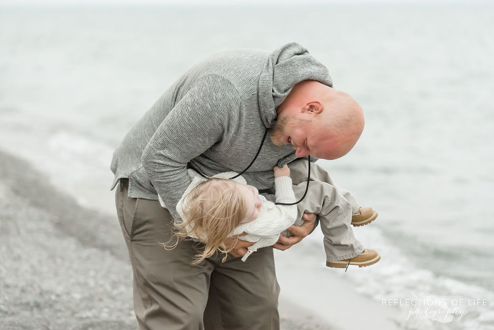 Father looking down at toddler son in Grimsby Ontario Canada on the beach.jpg