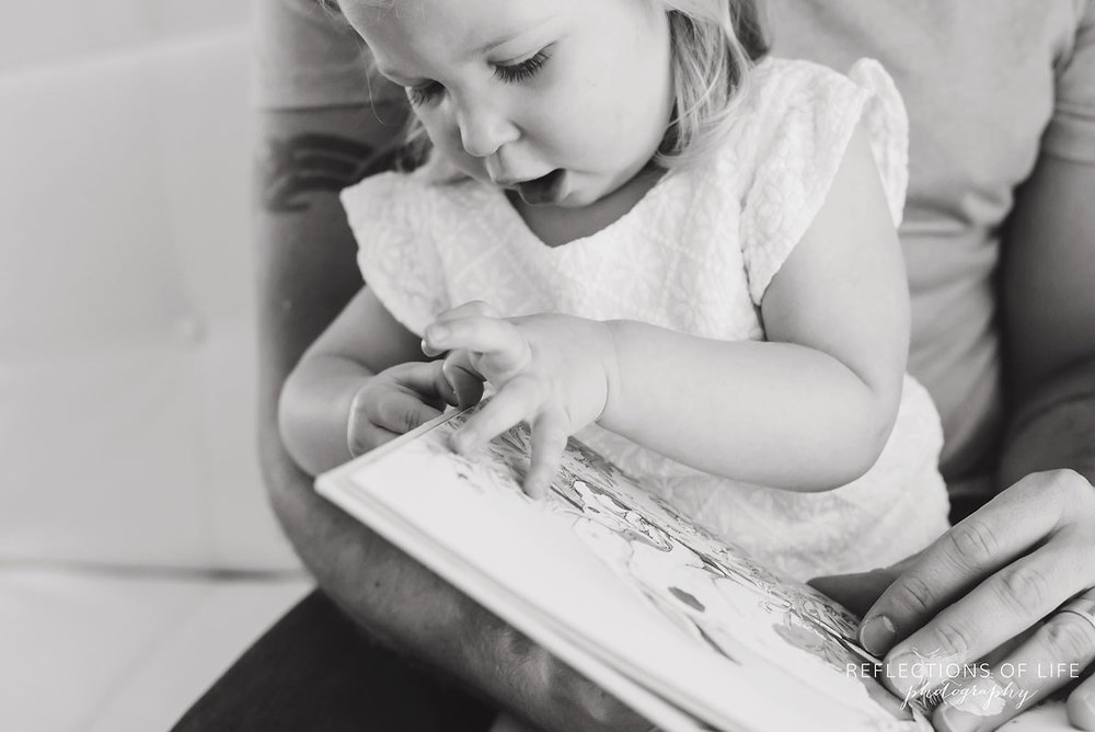 006 Photo of little girl turning the pages of a storybook in Niagara Region of Ontario Canada.jpg