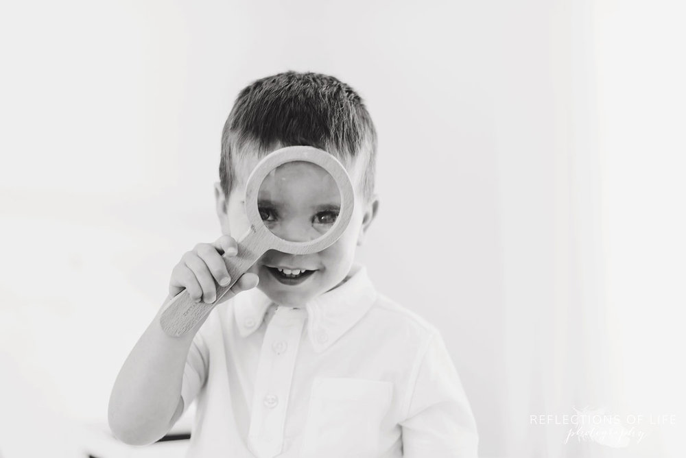 Black and white of little boy looking through a magnifying glass