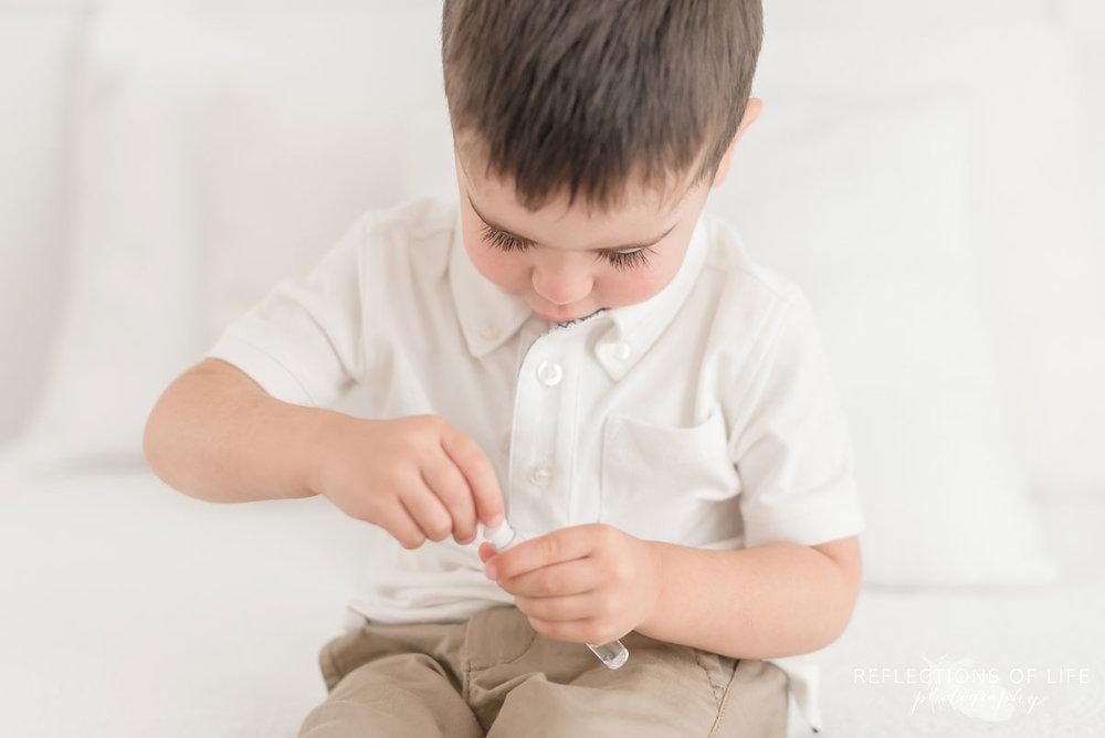 Colour photo of little boy blowing bubbles
