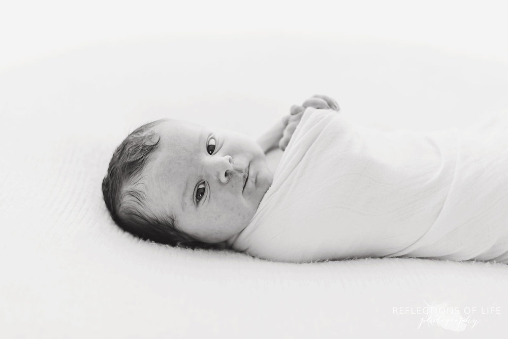 Black and white photo of  little newborn baby girl looking straight at the camera