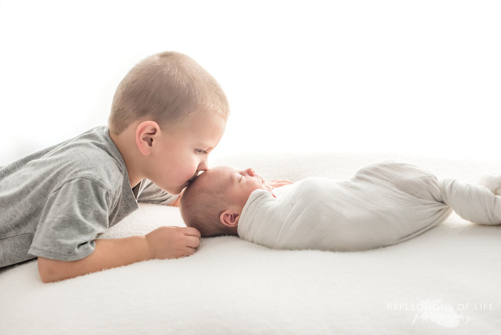Big brother giving his newborn baby brother a kiss on the head