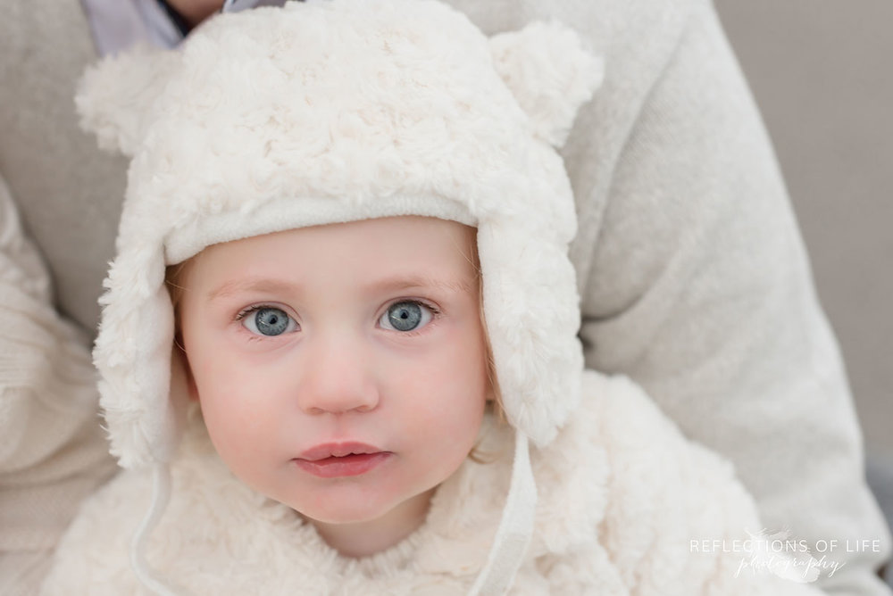 Little girl in adorable white hat in winter