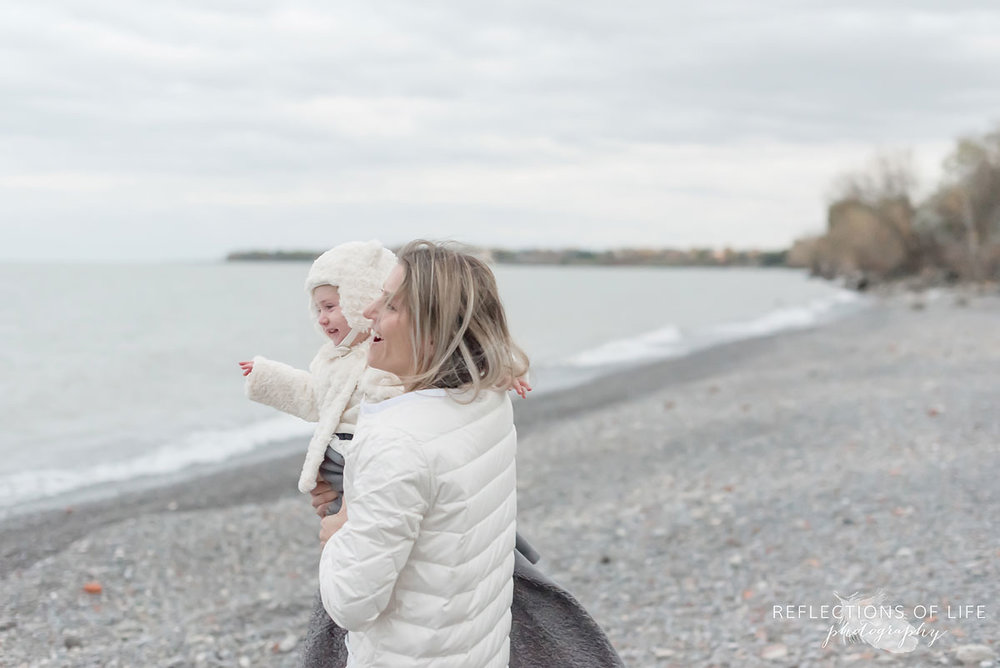 Mom laughing with her little girl on the beach in winter