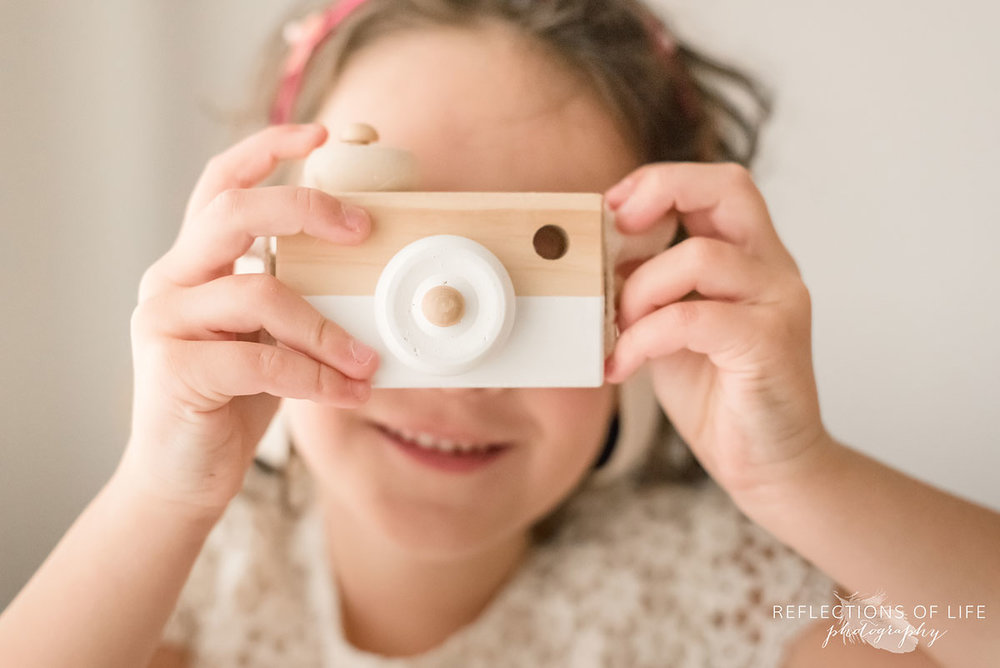 young girl holding toy camera