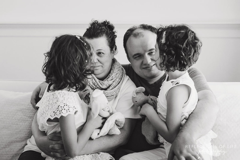 twin girls sitting on parents laps black and white
