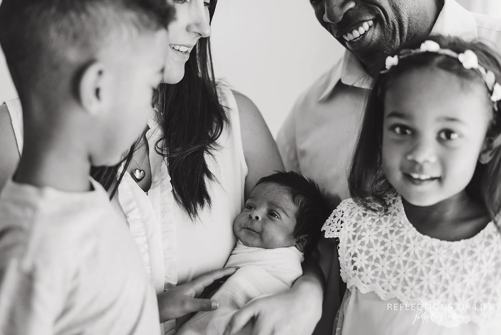 black and white happy family surounding baby