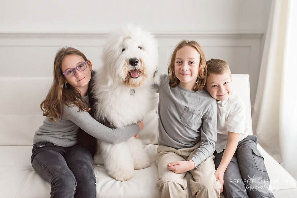 happy bothers and sister hugging old english sheepdog
