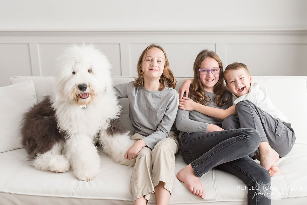 old english sheepdog sitting beside three happy smiling kids on couch